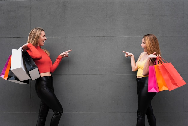 Girls with shopping bags pointing at each other Free Photo