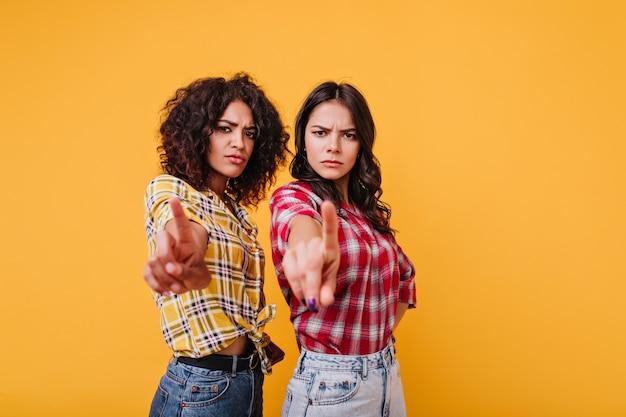 Девушки с суровым выражением лица показывают знак остановки. подруги укоризненно смотрят, показывая указательные пальцы Бесплатные Фотографии