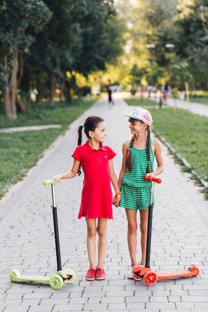 Girls with their push scooters holding each other's hand in the park Free Photo