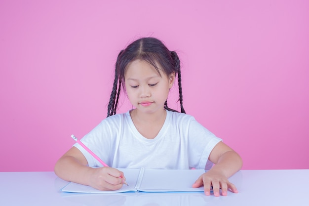 Girls write books on a pink background. Free Photo