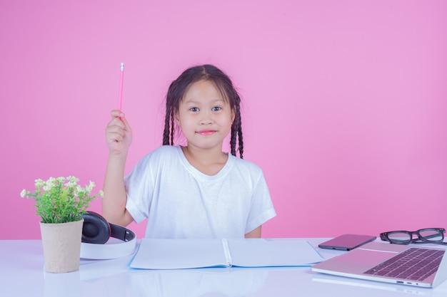 Girls write books on a pink background. Free Photo