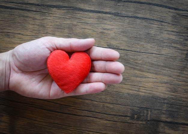 Give love man holding red heart in hands for love valentines take care Premium Photo