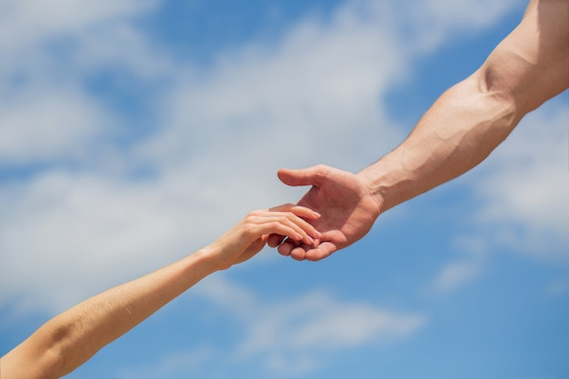 救いの手を差し伸べる。青い空を背景に男女の手。 Premium写真