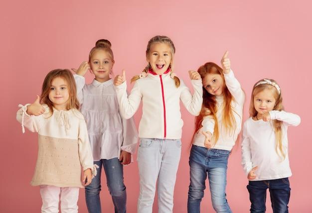 Дарить и получать подарки на рождественские праздники. группа счастливых улыбающихся детей, весело проводящих время, празднуя изолированные на розовом фоне студии. встреча нового 2021 года, детство, счастье, эмоции. Бесплатные Фотографии