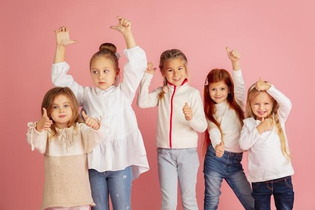 クリスマス休暇にプレゼントを贈ったり受け取ったりする。ピンクのスタジオの背景に孤立して祝って、楽しんで幸せな笑顔の子供たちのグループ。 2021年の新年の会議、子供時代、幸福、感情。 無料写真