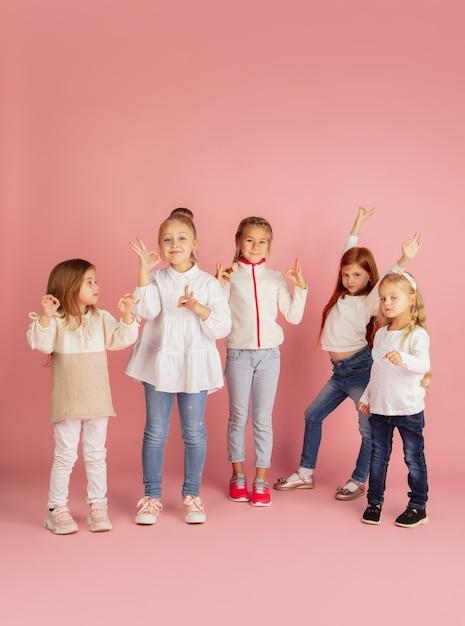 Dare e ricevere regali durante le vacanze di natale. gruppo di bambini sorridenti felici divertendosi, celebrando isolato su sfondo rosa studio. incontro di capodanno 2021, infanzia, felicità, emozioni. Foto Gratuite