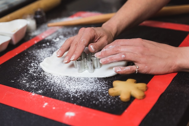 女性は、アイシング砂糖gl薬スノーフレークでクリスマスジンジャーブレッドクッキーを飾ります。クリスマスプレゼント、自家製ジンジャーブレッド Premium写真