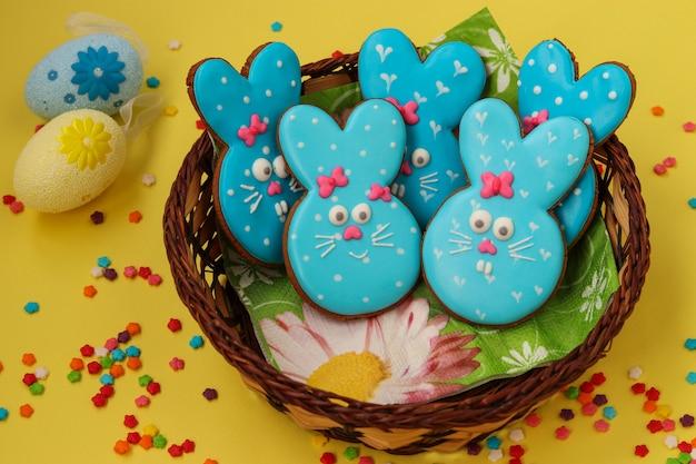 イースター面白い青いウサギ、自家製の塗装ジンジャーブレッドビスケット、黄色の背景に枝編み細工品バスケットでgl薬 Premium写真