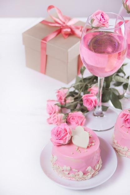 ピンクのgl薬、美しいバラ、コーヒー、白いテーブルの上のギフトボックスとミニの小さなケーキ。 Premium写真