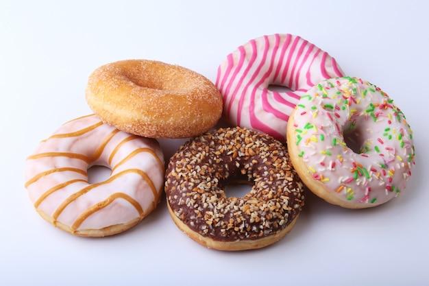 Gl薬、カラフルな振りかける、白い背景で隔離のナッツのおいしい自家製ドーナツの盛り合わせ。 Premium写真