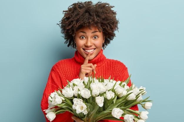 巻き毛の嬉しいアフロアメリカ人女性は、沈黙のジェスチャーをし、広い笑顔を見せ、赤いジャンパーを着て、青い壁に隔離された白い春のチューリップを持っています。誰が花を贈ったのか教えてくれません 無料写真