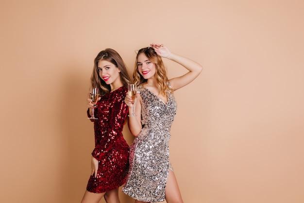 파티 사진 촬영 동안 곱슬 자매 옆에 서있는 아름다운 빨간 드레스에 기쁜 갈색 머리 여자 무료 사진
