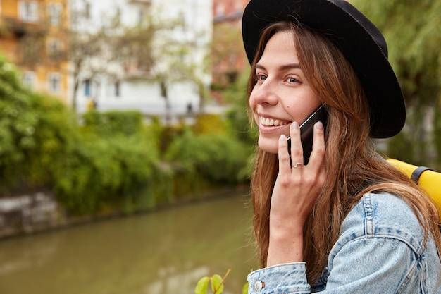 嬉しい魅力的な女性観光客は、街の小さな川の背景に立ち、携帯電話で会話し、ローミング接続を使用します 無料写真