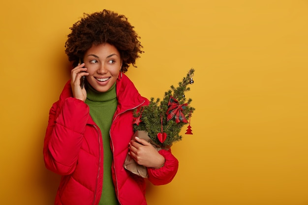 다행 곱슬 머리 여자가 전화 통화를하고 크리스마스를위한 작은 장식 된 Firtree를 보유하고 있습니다. 무료 사진