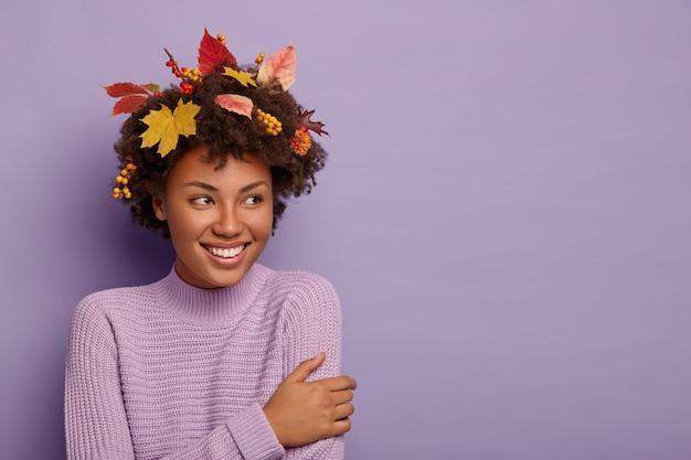 Felice donna dai capelli ricci si gira da parte, ha uno sguardo gioioso, si compiace di qualcosa di fantastico, indossa abiti casual, foglie d'acero sulla testa, sorride piacevolmente, posa al coperto Foto Gratuite