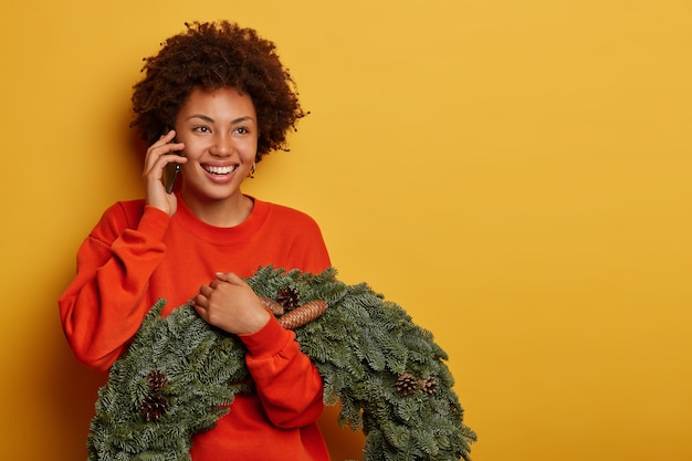 Glad curly woman enjoys telephone conversation, discusses christmas preparation with friend, holds fir handmade wreath with pine cones, stands against yellow background Free Photo