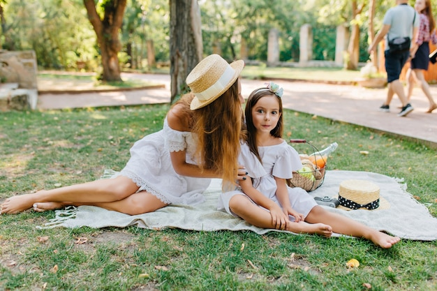 嬉しい黒髪の女の子が母親の近くの毛布の上に座って、彼女の足に触れています。ファッショナブルな若い女性と人々と草の上でポーズをとる白いドレスのかわいい娘の屋外家族の肖像画。 無料写真