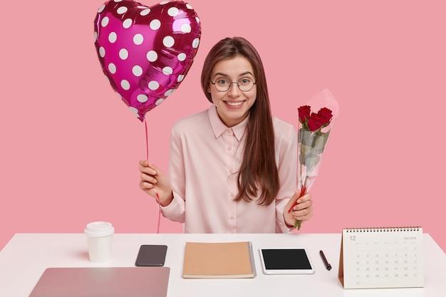 嬉しい黒髪の女性は楽しい表情をしていて、プレゼントを受け取って喜んでいると感じ、バレンタインと赤いバラを運びます 無料写真