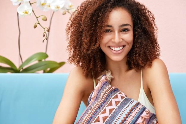 Felice femmina riccia dalla pelle scura con un ampio sorriso luminoso, abbraccia il cuscino mentre si siede su un comodo divano contro il muro rosa. Foto Gratuite