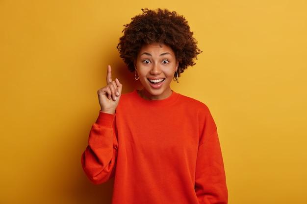 アフロヘアカットのうれしい暗い肌の女性は素晴らしい製品をお勧めします、満足のいくポイント、赤いセーターを着て、黄色のスタジオの壁に隔離された完璧なプロモーションを示しています 無料写真