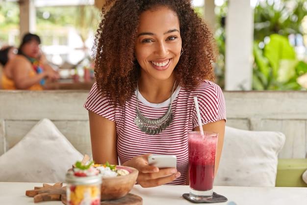 Felice donna dalla pelle scura con capelli croccanti, legge le notizie sul sito web, si connette a internet wireless alla caffetteria, beve frullati freschi, posa al ristorante con terrazza, installa l'app, indossa una maglietta, una collana Foto Gratuite