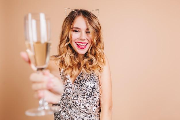Радостная европейская женщина со светлыми вьющимися волосами поднимает бокал с улыбкой у светлой стены Бесплатные Фотографии