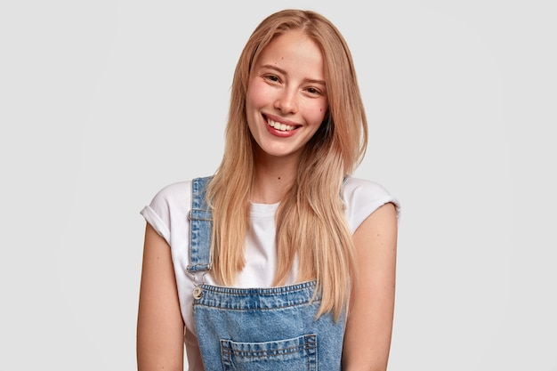 Glad european young woman with satisfied expression, smiles broadly, has healthy pure skin, dressed in denim stylish overalls Free Photo