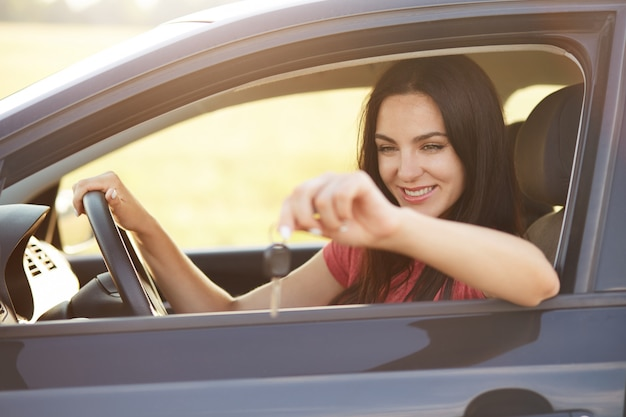 Glad female driver holds keys from car Free Photo