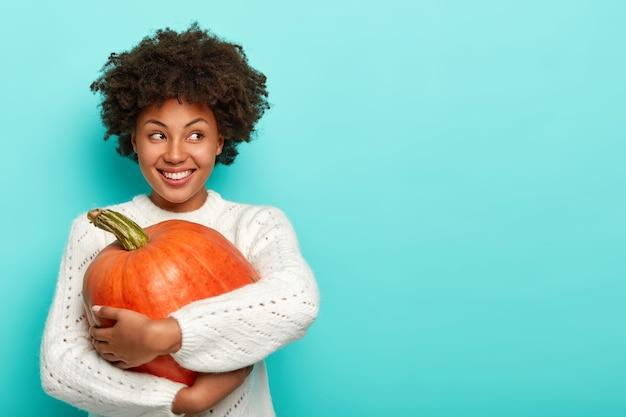 Довольная женщина с прической афро, держит большую тыкву, использует здоровые продукты для приготовления натуральной еды, счастливо смотрит в сторону, одетая в свитер Бесплатные Фотографии