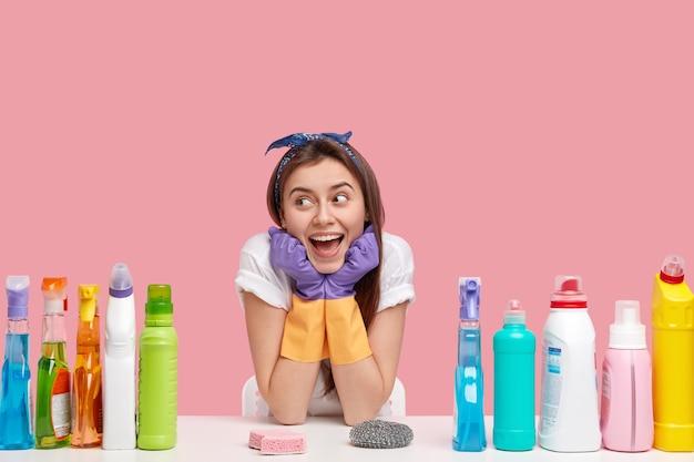 기쁜 여성 관리인은 손을 턱 밑에 두르고, 행복하게 외모를하고, 머리띠와 캐주얼 티셔츠를 입고, 청소를 위해 세제와 스폰지를 사용하고, 분홍색 벽 위에 격리되어 있습니다. 가정용 개념. 무료 사진