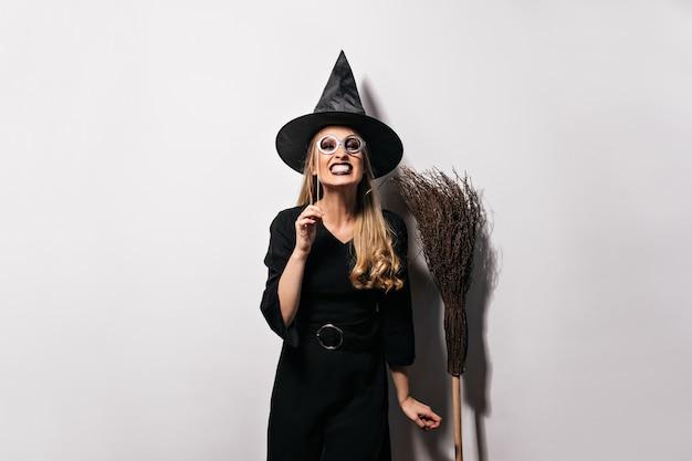 Радостная женская модель в смешном позе костюма хеллоуина. эмоциональная блондинка в шляпе ведьмы, стоя на белой стене. Бесплатные Фотографии