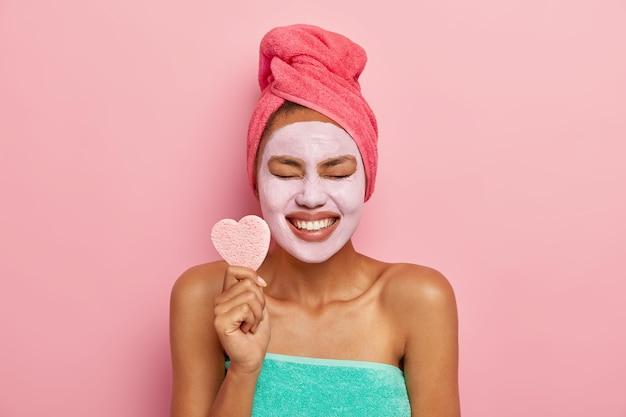 Glad female model smiles broadly, shows white teeth, holds heart shaped cosmetic sponge, keeps eyes shut from pleasure Free Photo
