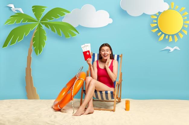 기쁜 여성 여행자가 해변 의자에 앉아 비행 티켓으로 여권을 보유하고 있습니다. 무료 사진