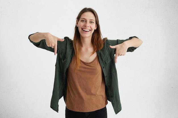 楕円形の顔、緑のジャケットと茶色のシャツを着た暗いストレートの髪をした女性は、人差し指で陽気な表情をしています。 無料写真