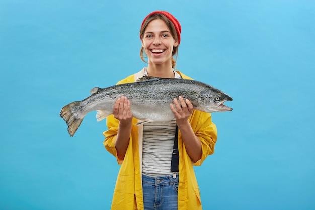 黄色いアノラックを身にまとううれしそうな漁師の女性。巨大な魚を捕まえて喜んで巨大な魚を手にし、青い壁の上に立っている彼女の作品を示しています。人、趣味、レクリエーション、釣り 無料写真