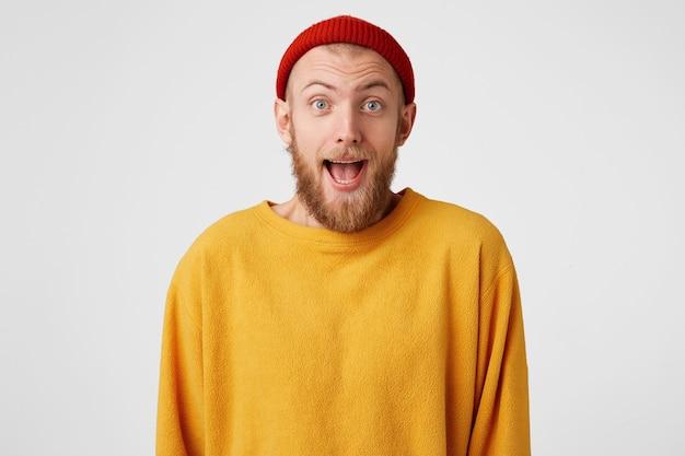 Радостный рыжий мужчина со счастливым изумленным выражением лица носит красную шляпу и повседневный свитер, радуется успешно выполненному проекту. Бесплатные Фотографии