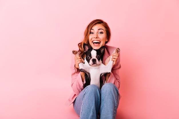 面白い小さな犬と遊ぶジーンズのうれしい女の子。彼女の子犬と一緒に時間を過ごす巻き毛の髪型を持つ興奮した生姜の女性の屋内の肖像画。 無料写真