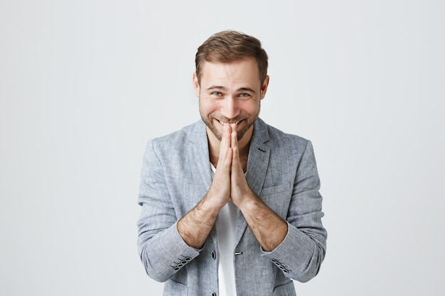 Glad happy man thanking, bow with hands in plead Free Photo