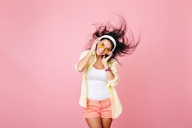黒髪を振って笑ってポーズをとるカラフルな服を着たうれしいラテンの女の子。楽しんでいるヘッドフォンでアジアの女性モデルを喜ばせる 無料写真