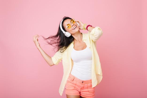 ダンスを振って何かを夢見ている黒髪のうれしいラテン女性。音楽と笑顔を楽しんでいるカラフルなアクセサリーで陽気な女性 無料写真