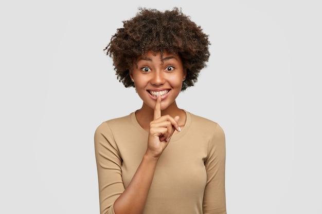 기쁜 사랑스러운 아프리카 계 미국인 여성은 침묵을 유지하고 입술에 검지 손가락을 들고 캐주얼 한 옷을 입고 쾌활한 표정을 지으며 흰 벽에 포즈를 취합니다. 사람, 비밀 및 민족성 개념 무료 사진