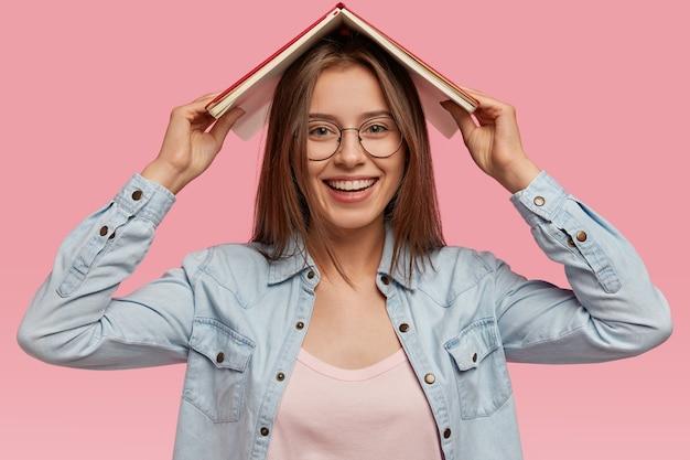 Felice e adorabile giovane donna porta il libro sopra la testa, sorride dolcemente, si diverte a leggere storie interessanti, indossa abiti eleganti, modelle contro il muro rosa, prova piacere dal suo hobby preferito Foto Gratuite