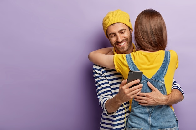 Felice imbroglione invia un messaggio di testo all'amante mentre abbraccia la moglie, ha una chat segreta dietro le amiche, tiene in mano il cellulare moderno Foto Gratuite