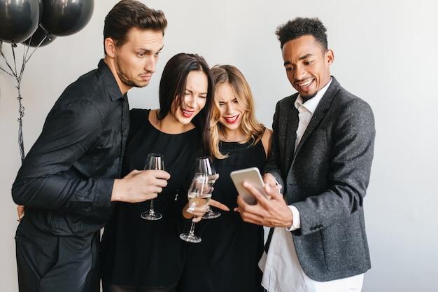 Счастливый человек показывает друзьям последние фотографии на своем телефоне во время вечеринки Бесплатные Фотографии
