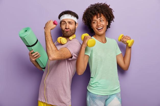 嬉しい多民族の夫と妻はスポーツセンターに出席し、ダンベルで運動し、フィットネスマットを持ち、お互いに立ち向かい、面白い幸せそうな顔つきをし、tシャツを着て、紫色の壁に隔離されています 無料写真