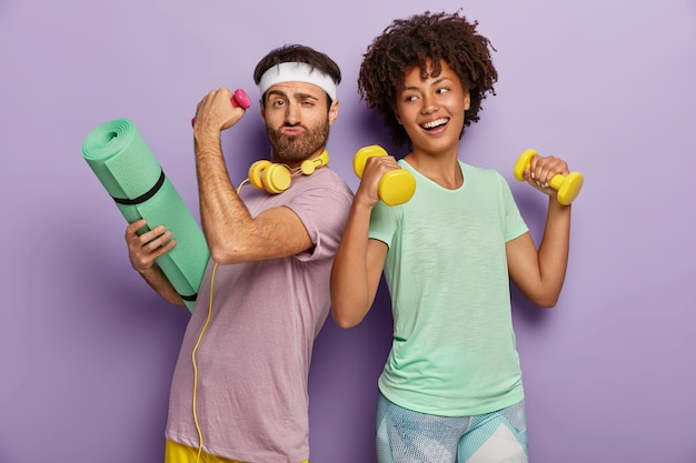 Felice marito e moglie multietnici frequentano un centro sportivo, si esercitano con i manubri, tengono il tappetino fitness, si guardano l'un l'altro, hanno un aspetto divertente e felice, indossano magliette, isolato sul muro viola Foto Gratuite