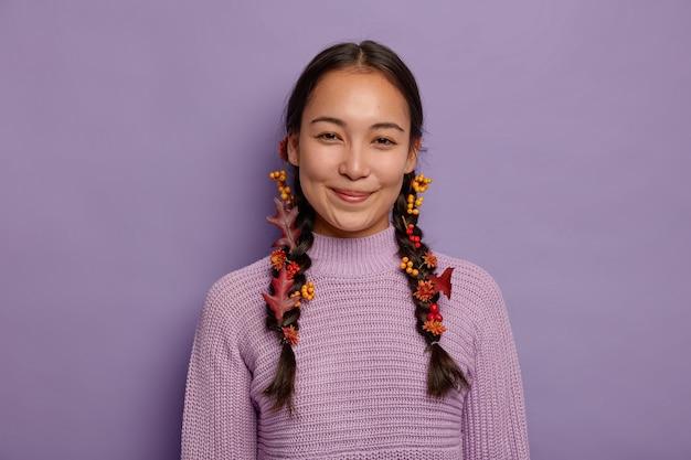 기쁜 자연 아시아 여성이 가을을 축하하고, 붉은 단풍, 열매 및 꽃으로 장식 된 두 개의 주름이 있고 보라색 벽에 고립 된 보라색 스웨터를 입습니다. 10 월 시간 무료 사진