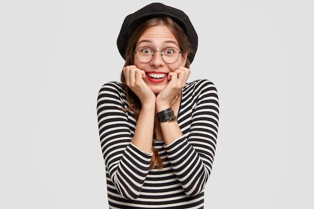 Довольная парижанка обеими руками касается подбородка, у нее сияющая улыбка, веселое выражение лица, она одета в повседневную одежду во французском стиле. Бесплатные Фотографии