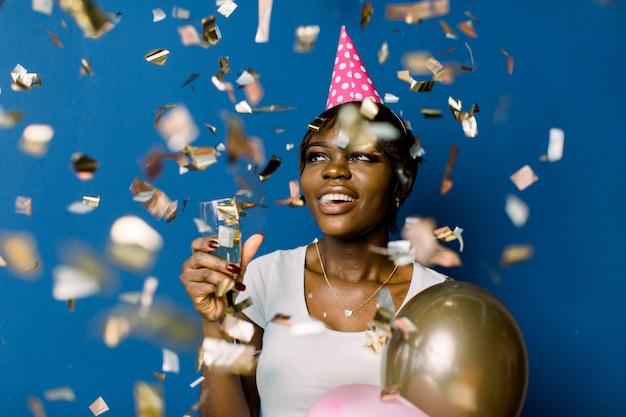 흰색 티셔츠 행복 춤과 색종이 밖으로 던지고, 생일을 축하 다행 꽤 아프리카 여자. 기쁘게 얼굴 표정으로 샴페인과 풍선을 들고 예쁜 흑인 아가씨의 실내 사진 프리미엄 사진