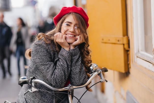 Радостная застенчивая девушка с брюнетками позирует на размытом фоне города в осенний день Бесплатные Фотографии